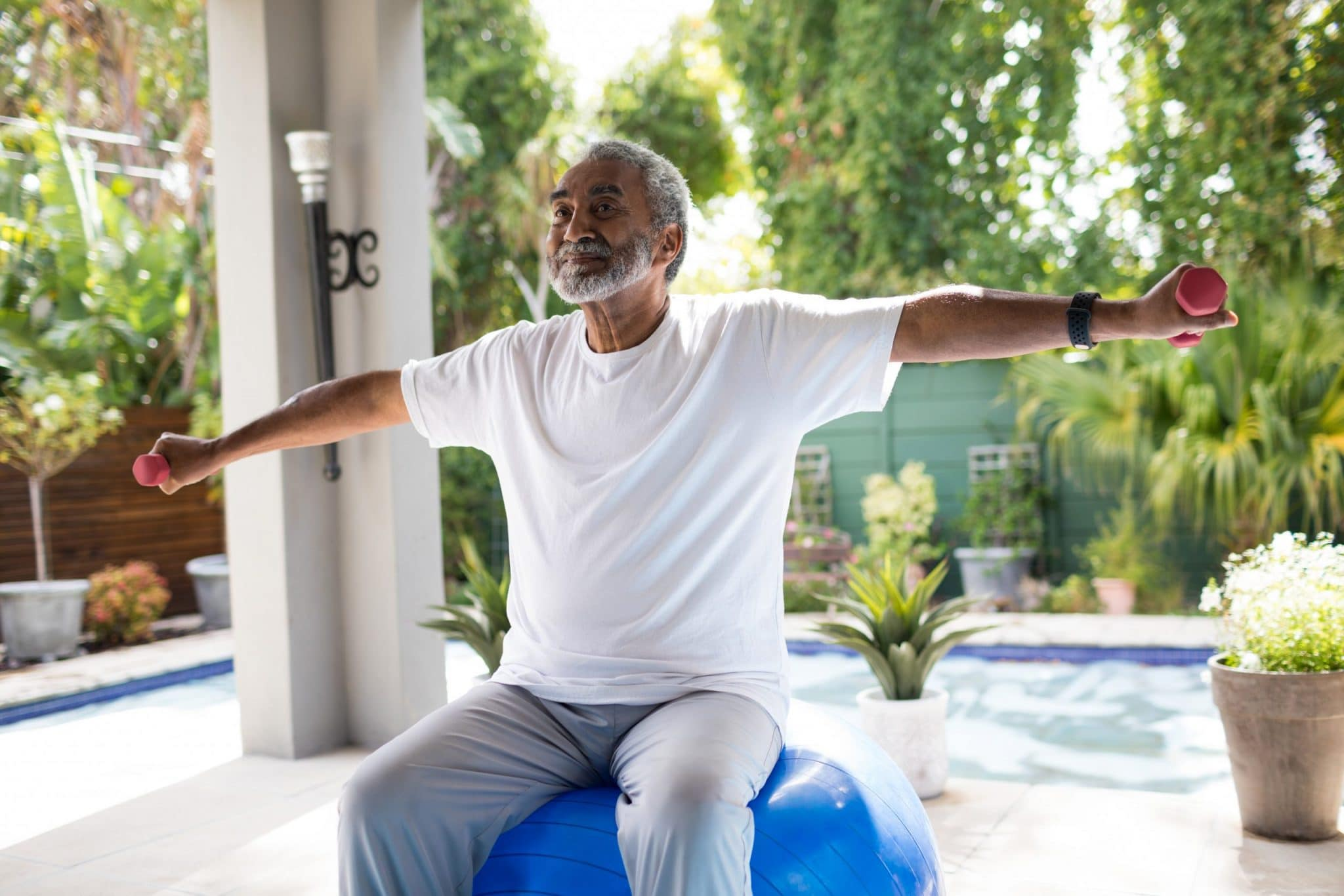 Senior man with arms outstretched lifting dumbbell